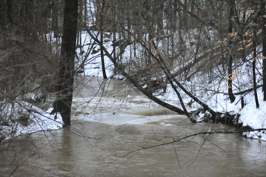 A few chunks of ice break free Wednesday as the Olentangy River fills its banks in Galion amid 45-degree weather.