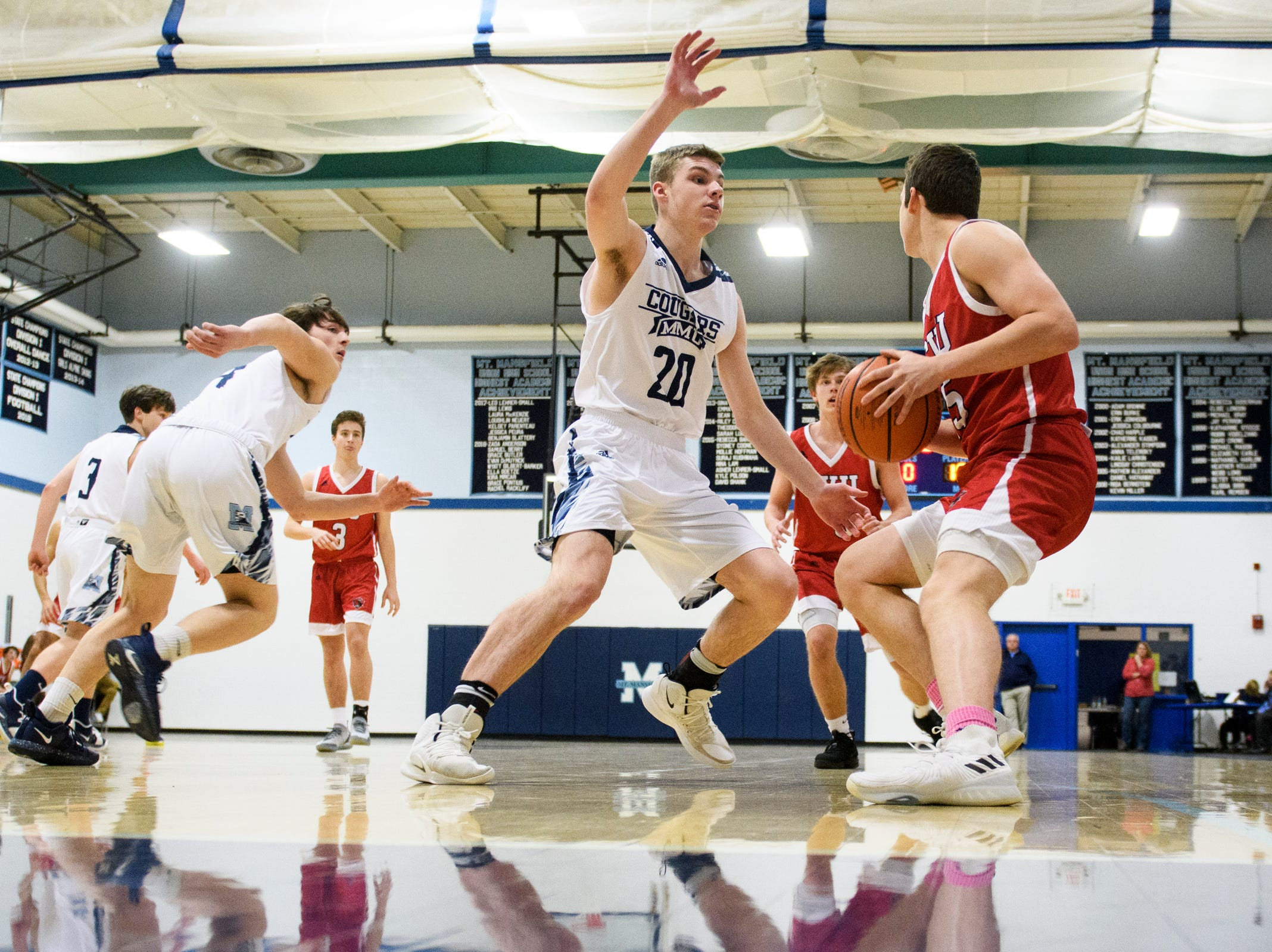 MMU's Connor Philbrick (20) tries to guard CVU's Bennett Cheer (15) during the boys basketball game between the Champlain Valley Union Redhawks and the Mount Mansfield Cougars at MMU High School on Tuesday night January 22, 2019 in Jericho.