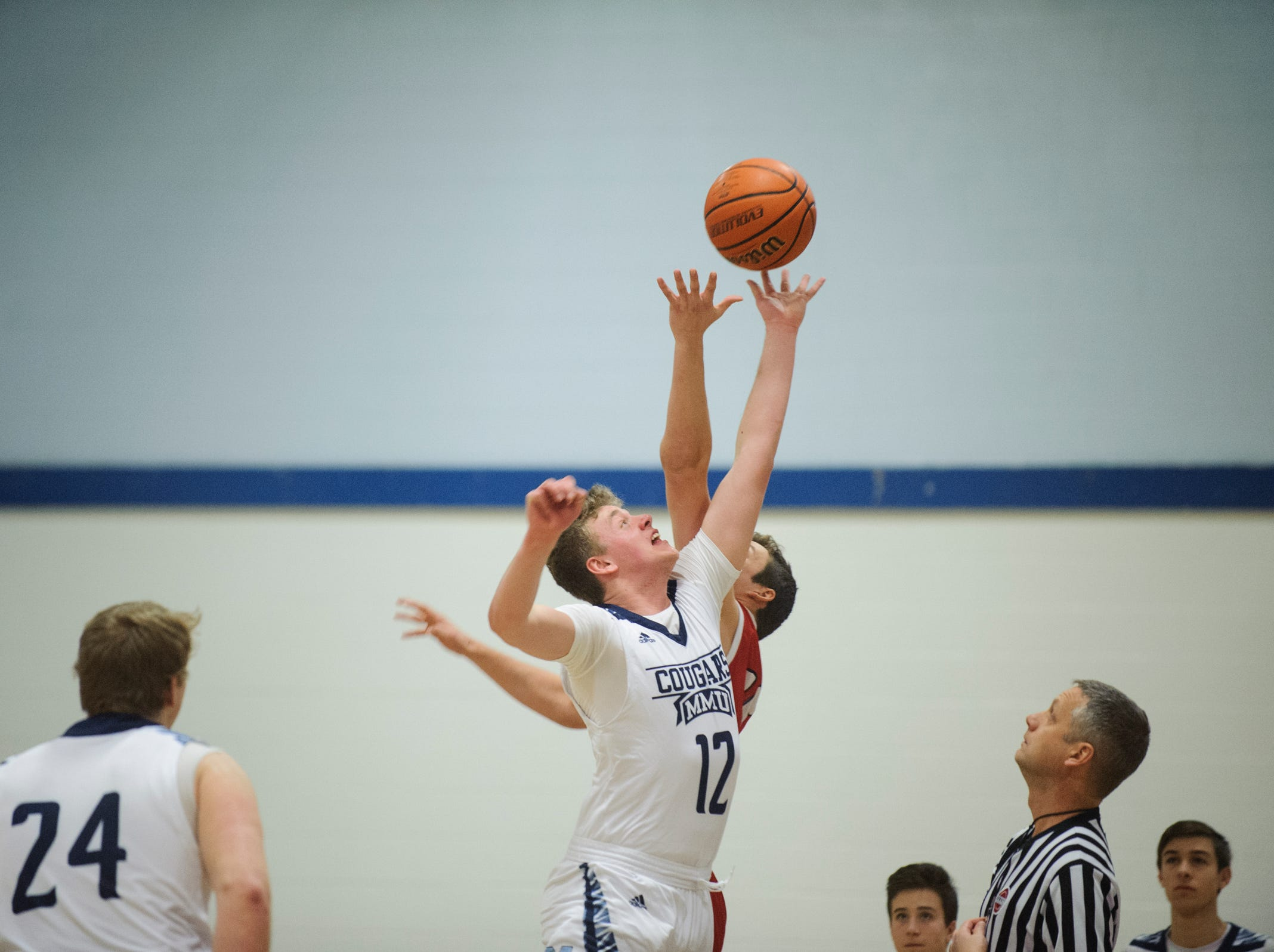 MMU's Asa Carlson (12) leaps for the opening tip off during the boys basketball game between the Champlain Valley Union Redhawks and the Mount Mansfield Cougars at MMU High School on Tuesday night January 22, 2019 in Jericho.