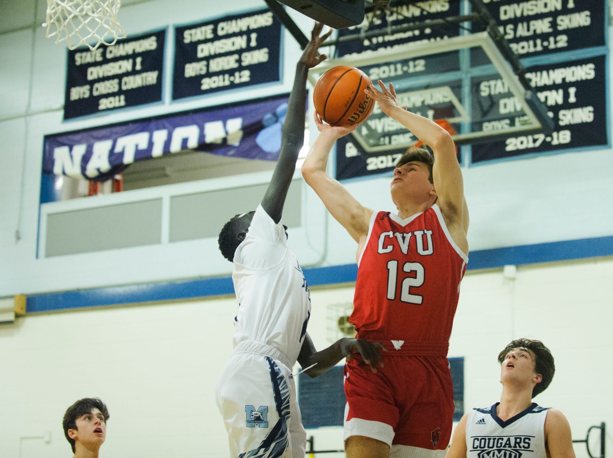 CVU's Alden Randall's (12) shot is blocked by MMU's Taylor Bowen (11)  during the boys basketball game between the Champlain Valley Union Redhawks and the Mount Mansfield Cougars at MMU High School on Tuesday night January 22, 2019 in Jericho.