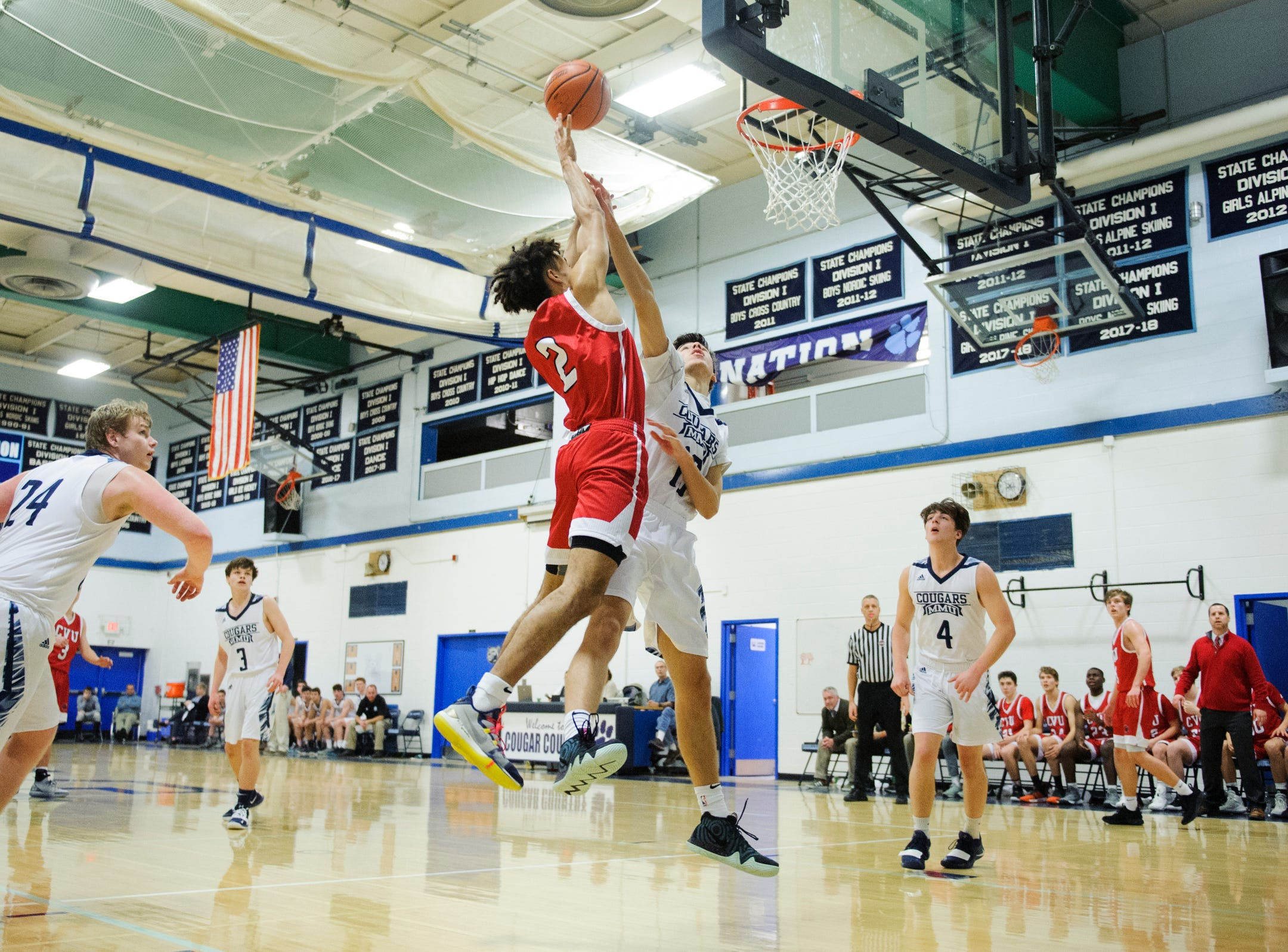 CVU's Jason West (2) leaps for a lay up over MMU's Becket Hill (13) during the boys basketball game between the Champlain Valley Union Redhawks and the Mount Mansfield Cougars at MMU High School on Tuesday night January 22, 2019 in Jericho.