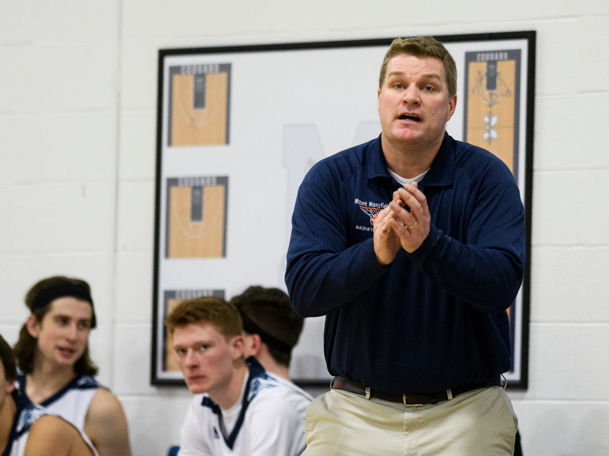 MMU head coach Jeff Davis talks to the team on the court during the boys basketball game between the Champlain Valley Union Redhawks and the Mount Mansfield Cougars at MMU High School on Tuesday night January 22, 2019 in Jericho.