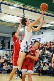 MMU's Harrison Leombruno-Nicholson leaps for a lay up over CVU's Ethan Harvey (5) and is called for a charge during the boys basketball game on Tuesday night January 22, 2019 in Jericho.