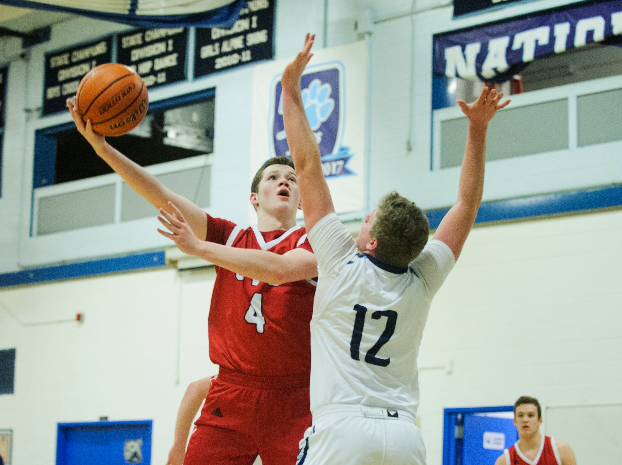 CVU's Mason Otley (4) leaps over MMU's Asa Carlson (12) for a lay up during the boys basketball game between the Champlain Valley Union Redhawks and the Mount Mansfield Cougars at MMU High School on Tuesday night January 22, 2019 in Jericho.