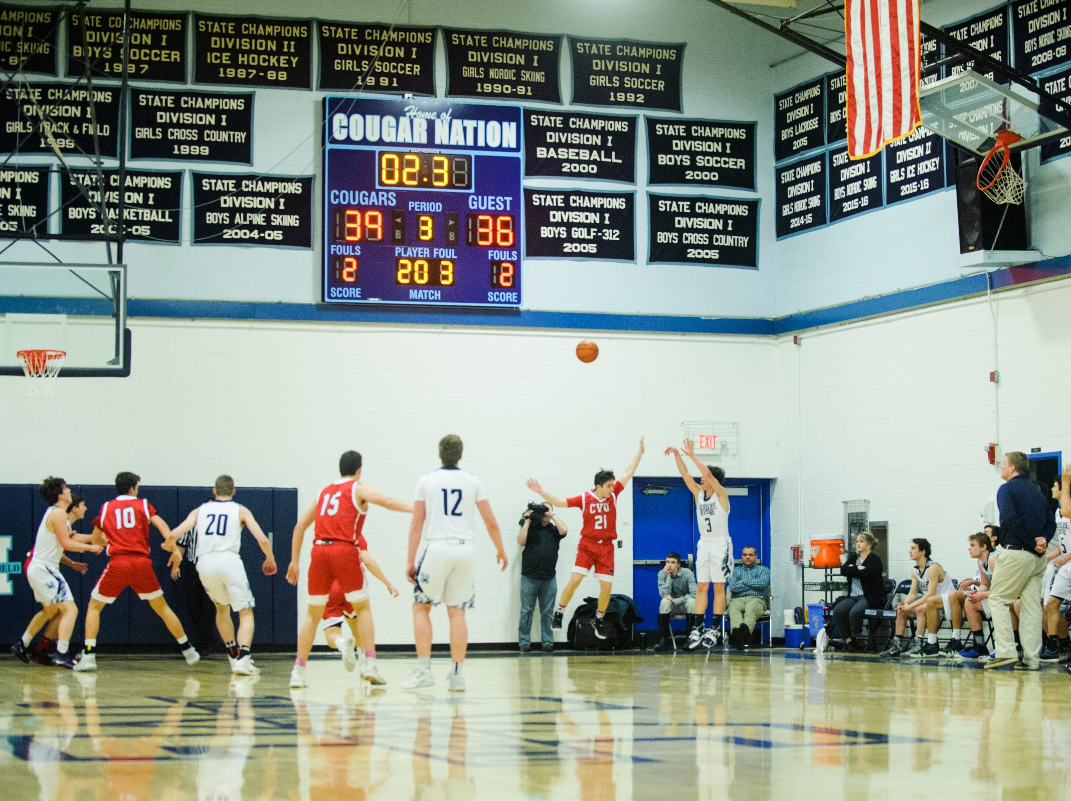 MMU's Justin Morse (3) shoots a three pointer over CVU's Nikos Carroll (21) during the boys basketball game between the Champlain Valley Union Redhawks and the Mount Mansfield Cougars at MMU High School on Tuesday night January 22, 2019 in Jericho.