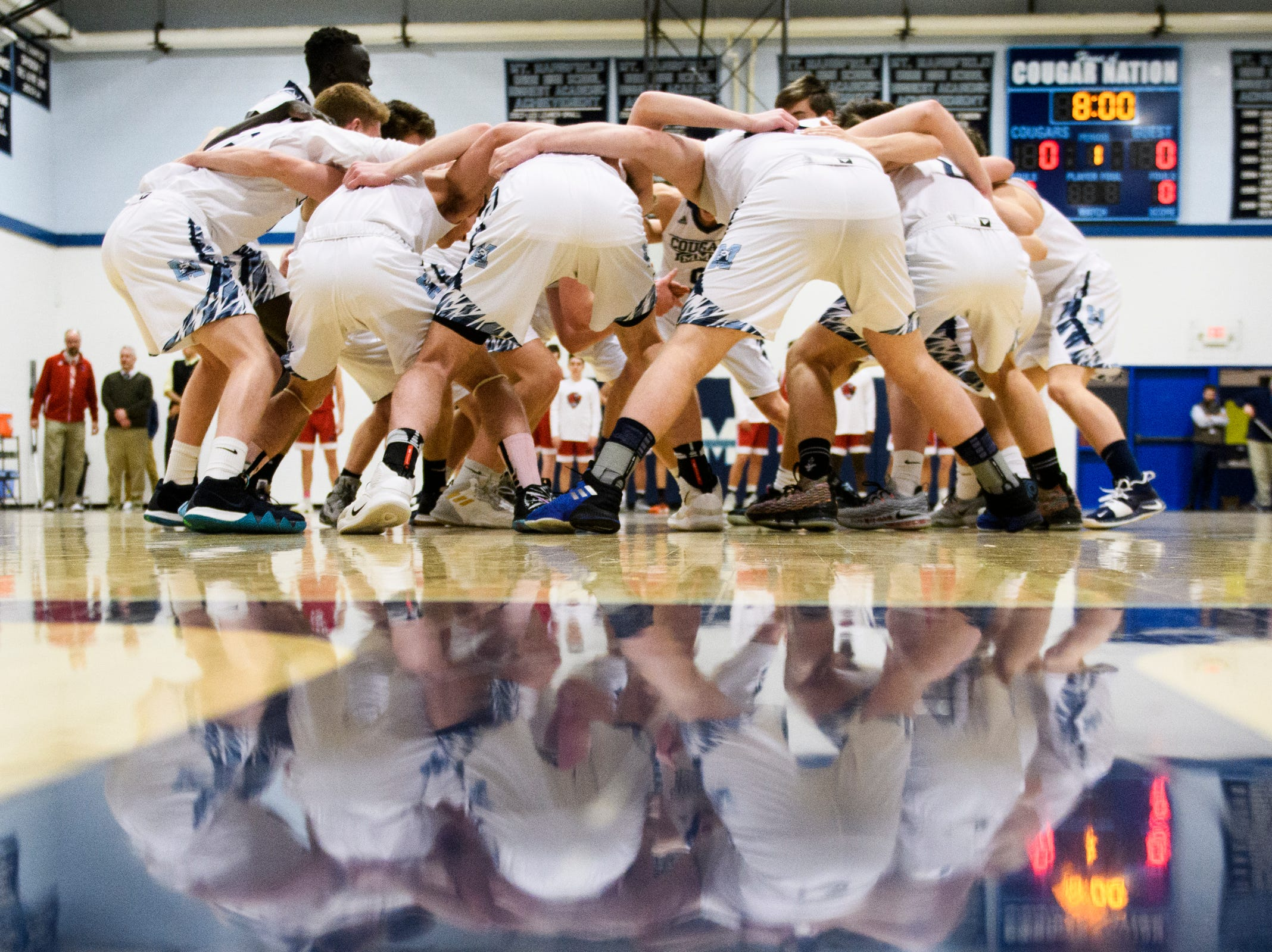 MMU huddles together during the boys basketball game between the Champlain Valley Union Redhawks and the Mount Mansfield Cougars at MMU High School on Tuesday night January 22, 2019 in Jericho.