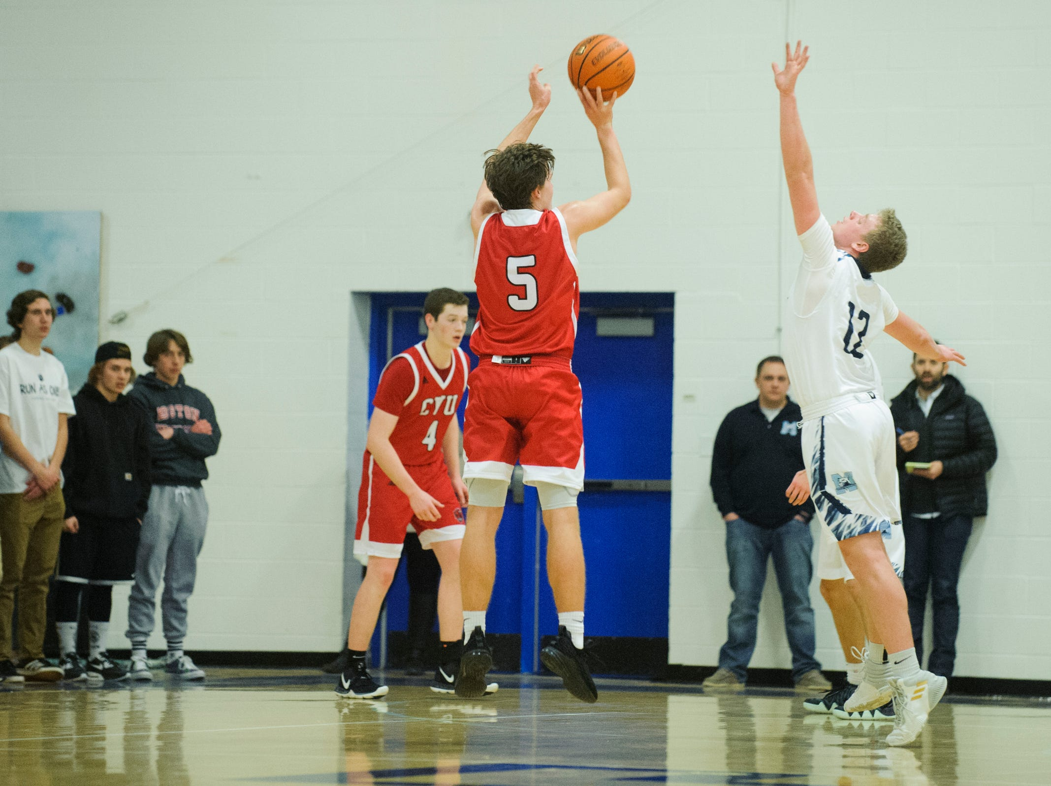 CVU's Ethan Harvey (5) shoots a three pointer over MMU's Asa Carlson (12) during the boys basketball game between the Champlain Valley Union Redhawks and the Mount Mansfield Cougars at MMU High School on Tuesday night January 22, 2019 in Jericho.