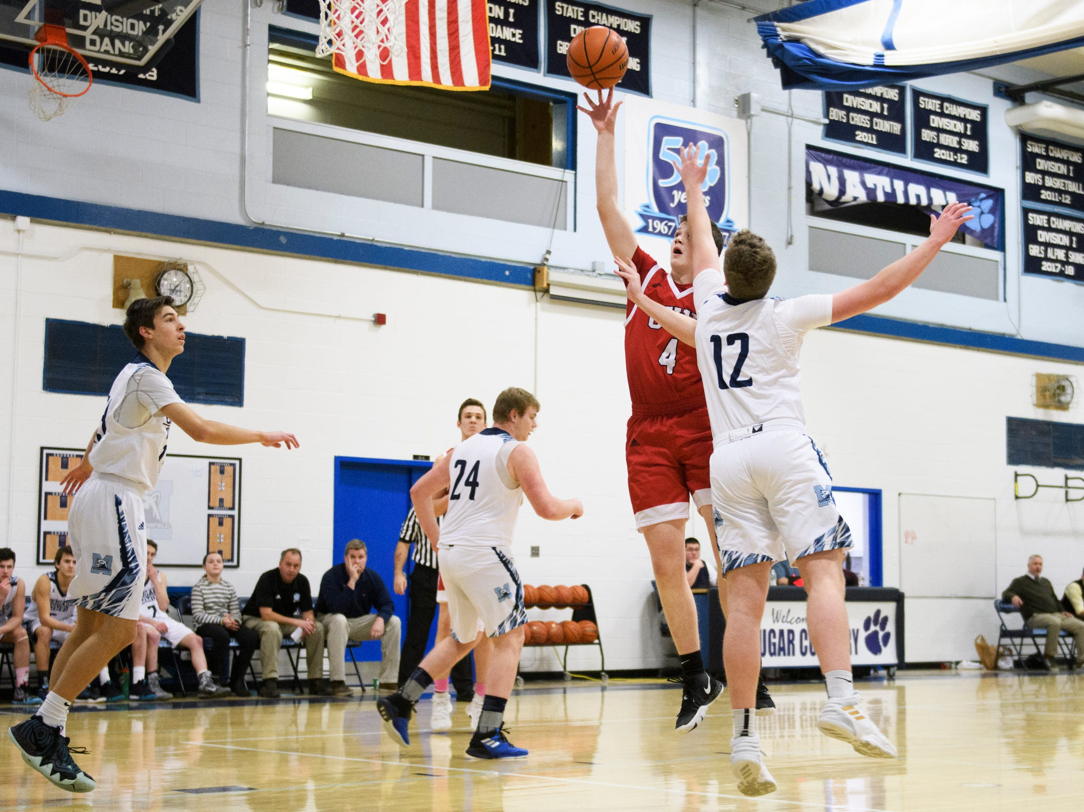 CVU's Mason Otley (4) leaps past MMU's Asa Carlson (12) to take a shot during the boys basketball game between the Champlain Valley Union Redhawks and the Mount Mansfield Cougars at MMU High School on Tuesday night January 22, 2019 in Jericho.