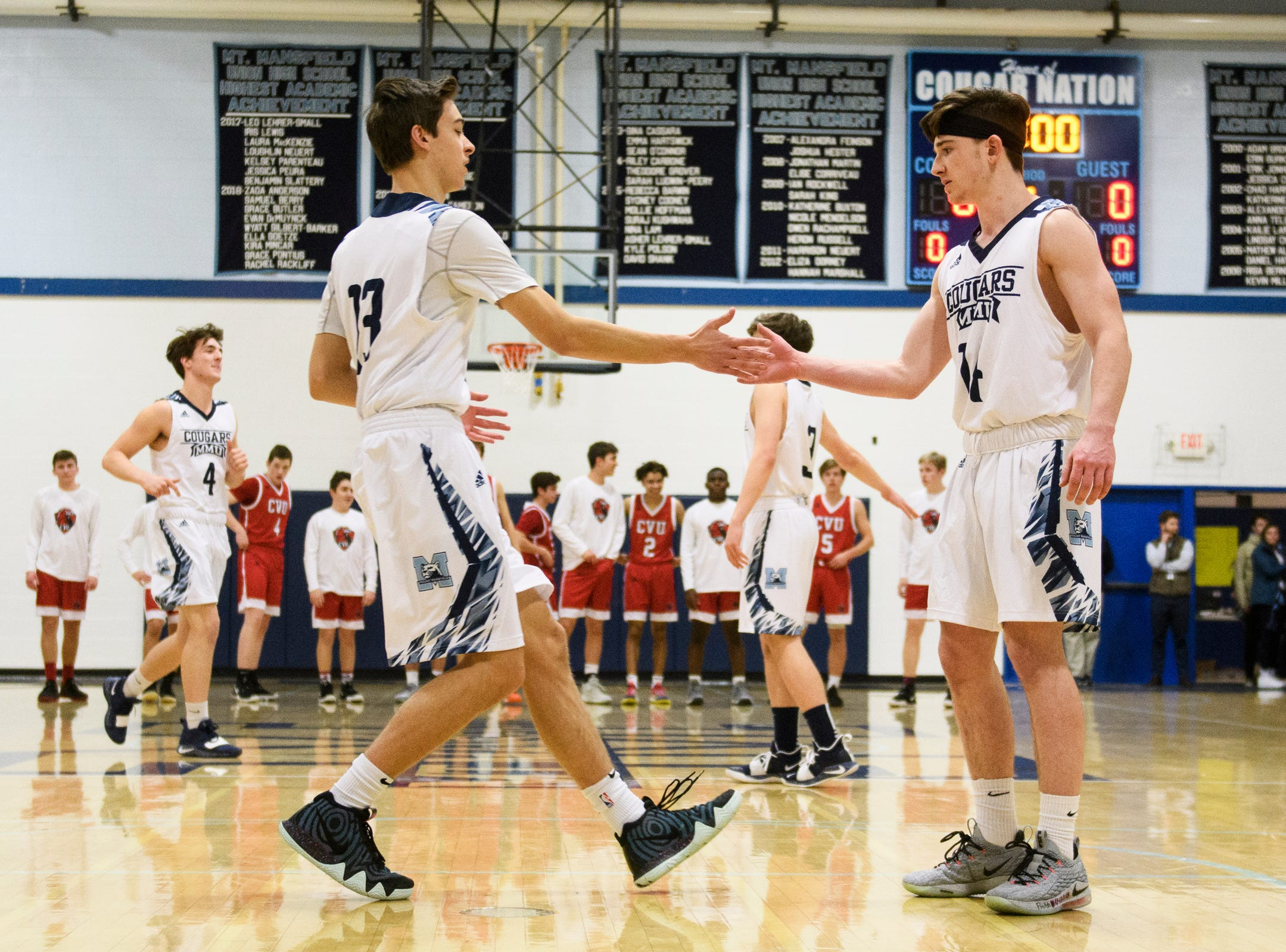 MMU's Becket Hill (13) is greeted by Mike Dix (14) as he takes the court during player introductions in the boys basketball game between the Champlain Valley Union Redhawks and the Mount Mansfield Cougars at MMU High School on Tuesday night January 22, 2019 in Jericho.