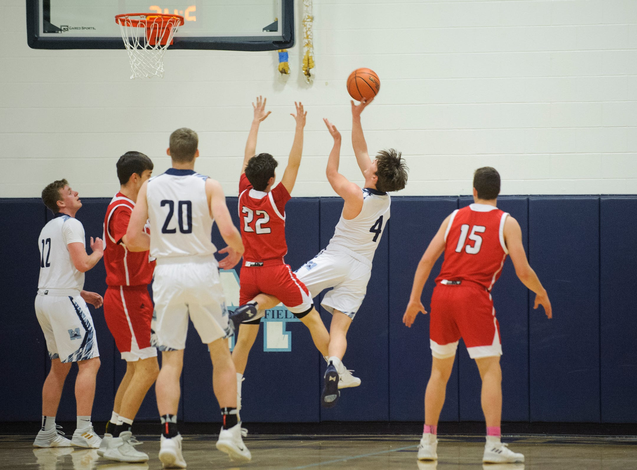 MMU's Harrison Leombruno-Nicholson (4) leaps for a lay up over CVU's Jacob Boliba (22) during the boys basketball game between the Champlain Valley Union Redhawks and the Mount Mansfield Cougars at MMU High School on Tuesday night January 22, 2019 in Jericho.