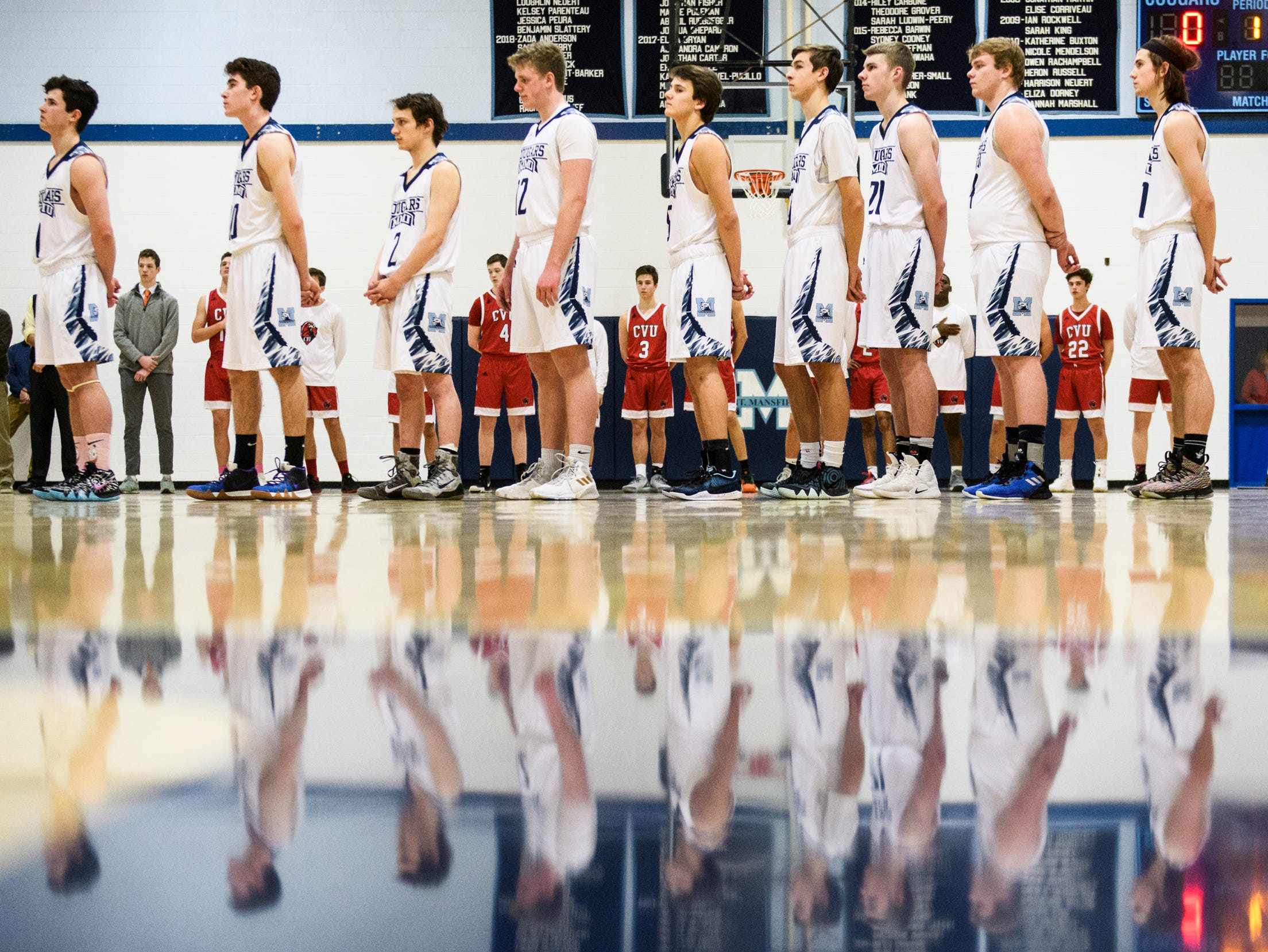 The teams listen to the Nation Anthem during the boys basketball game between the Champlain Valley Union Redhawks and the Mount Mansfield Cougars at MMU High School on Tuesday night January 22, 2019 in Jericho.