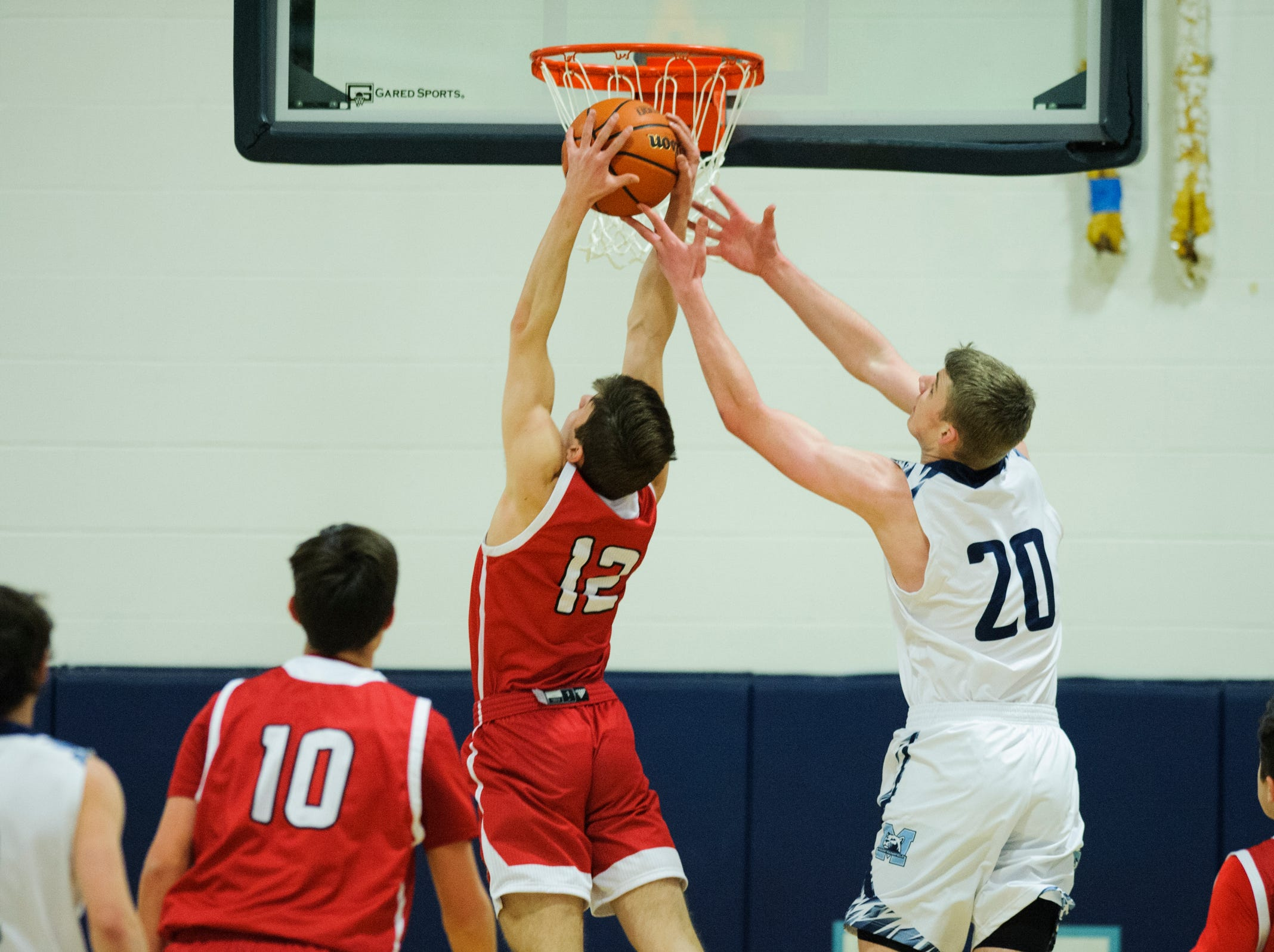CVU's Alden Randall (12) leaps to grab the rebound from MMU's Connor Philbrick (20) during the boys basketball game between the Champlain Valley Union Redhawks and the Mount Mansfield Cougars at MMU High School on Tuesday night January 22, 2019 in Jericho.