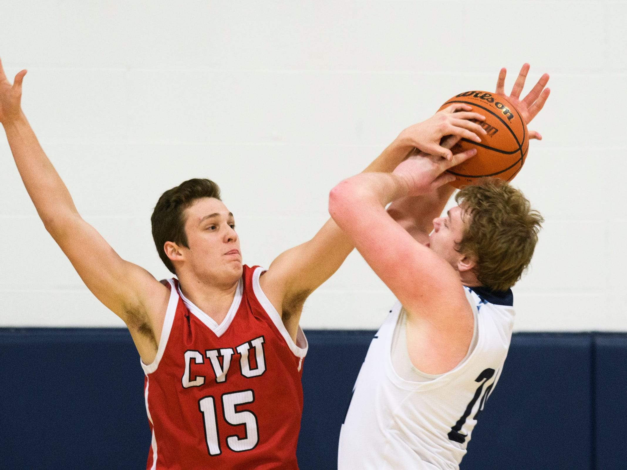 CVU's Bennett Cheer (15) blocks the shot by MMU's Mark Howland (12) during the boys basketball game between the Champlain Valley Union Redhawks and the Mount Mansfield Cougars at MMU High School on Tuesday night January 22, 2019 in Jericho.