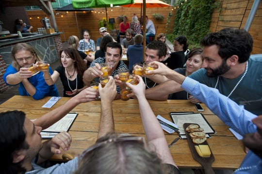 Mixology enthusiasts toast their old-fashioned cocktails in the beer garden at The Farmhouse Tap and Grill in Burlington on Tuesday, September 3, 2013.