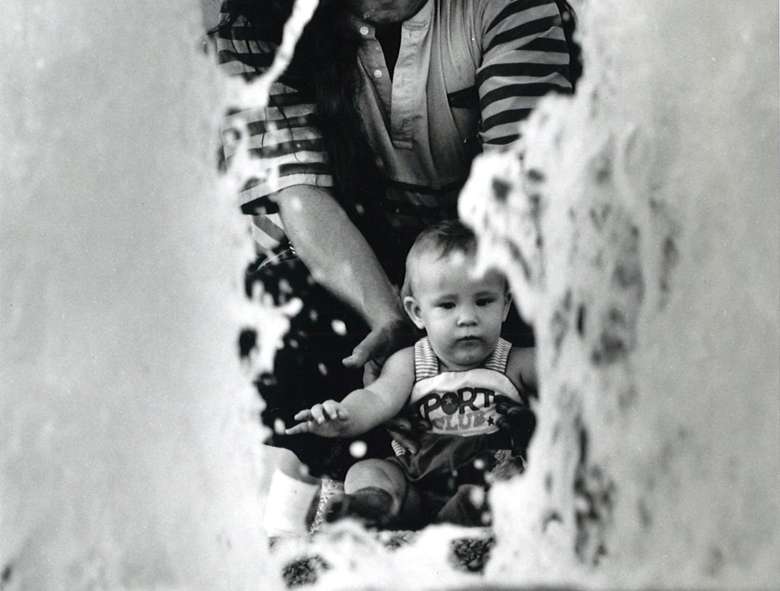 Victor Ramos Jr. holds his 10-month-old son Victor Ramos III to keep him from falling into the fountain at the Corpus Christi Watergarden on July 12, 1991.