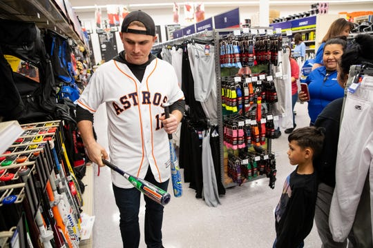 Houston Astros catcher Max Stassi helps a young boy pick out a bat at Academy Sports and Outdoors during the Astros' Caravan stop on Wednesday, Jan. 23, 2019.