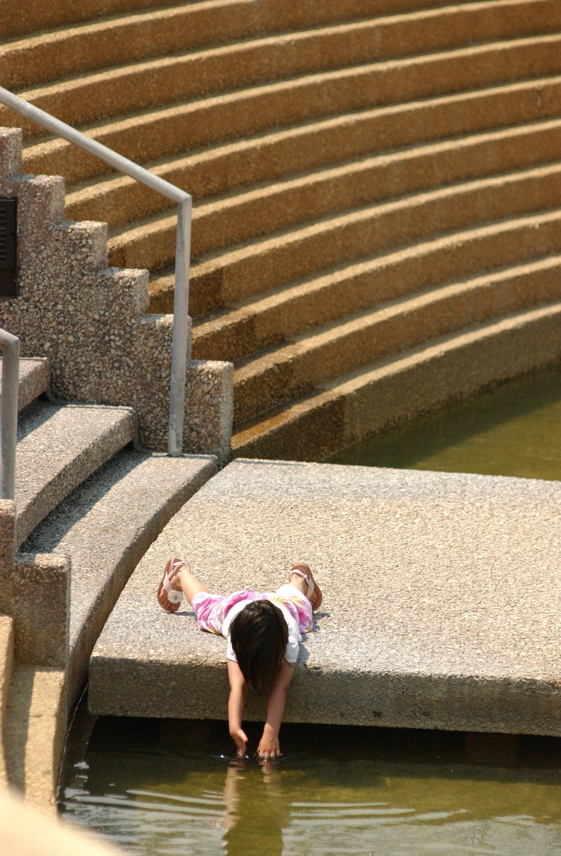 Frances Lee, 3, explores the Corpus Christi Watergarden in front of the Art Museum of South Texas June 21, 2005.