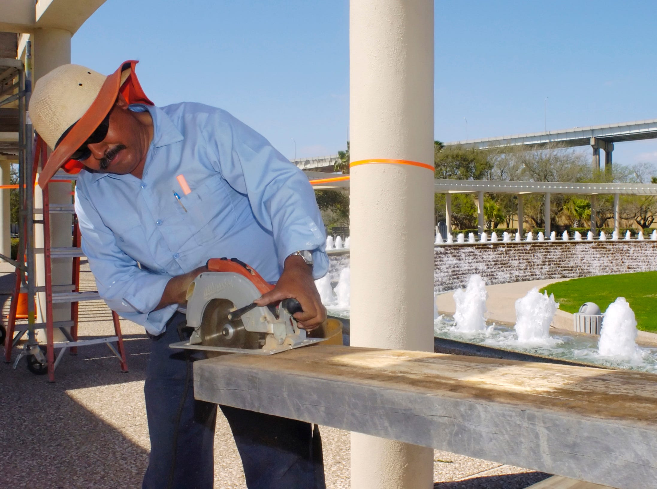 Marcelino Vaca, a city of Corpus Christi Parks Department employee, prepares a wooden beam that will replace rotted wood on an overhang at the Watergarden near the American Bank Center in 2006.