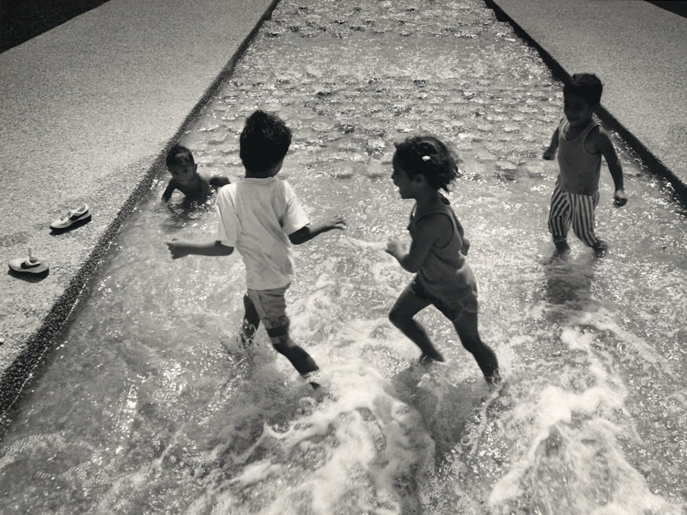 Mario Arredondo, 2, (left to right), Marco Lucas, 5, Marina Lucas, 4, and Mario Lucas, 3, play in the Watergarden in front of the Art Museum of South Texas on June 28, 1988.
