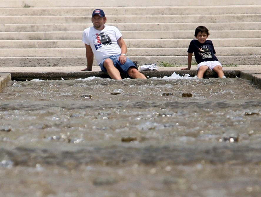 Travis Ramsey and his son, Travis Jr., 9, of Portland cool their feet off in the waters of the Corpus Christi museum district's Watergarden as temperatures reach into the upper 90's Sunday, Aug. 12, 2007.