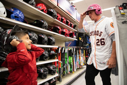 Astros's Myles Straw helps a Cesar Rodriguez pick out a batting helmet at Academy Sports and Outdoors during the Astros-Caravan stop on Wednesday, Jan. 23, 2019.