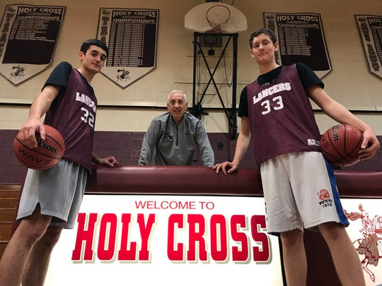 Junior Gianmarco Arletti, head coach John Valore and junior Giovanni Cessel have helped turn the Holy Cross boys' basketball program around this season.