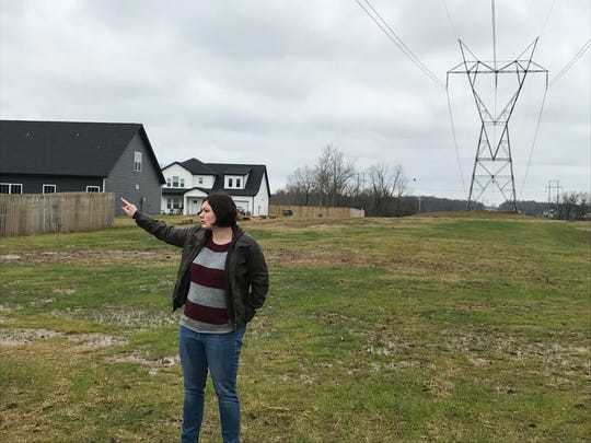 Eagles Bluff resident Caila Holm points out the new section of the neighborhood, while standing on the school zone boundary line that split the neighborhood until recently.