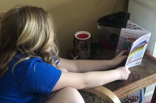 Elementary student Sadee Wheatley reading to her fish during the virtual snow day in Estherville, Iowa.