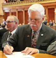 State Rep. Stan Gustafson signs the oath of office at the state Capitol. Gustafson, 76, has served in the Iowa House since 2014.