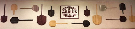 A wall inside Abbie's restaurant features assorted pizza peels.