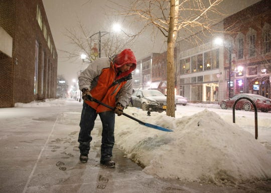 Marcelo Montero of Des Moines cleans snow off the sidewalk in Des Moines' East Village as snow fell across parts of central Iowa on Tuesday, Jan. 22, 2019.
