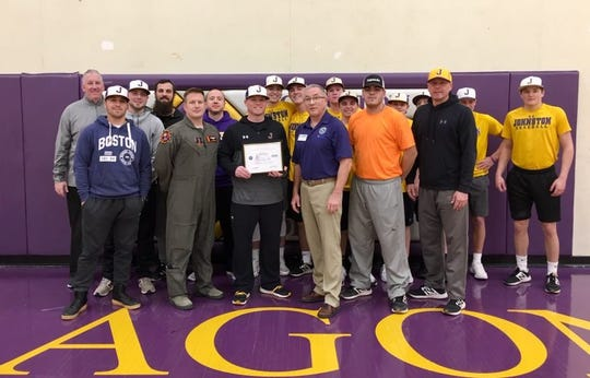 Johnston teacher and baseball coach Michael Barta, center, accepts his Patriot Award from Maj. Jon Harbart, Iowa Air Nation Guardsman and Jim Freese, of the Iowa Employer Support of the Guard and Reserve, on Jan. 21, 2019 at Johnston High.