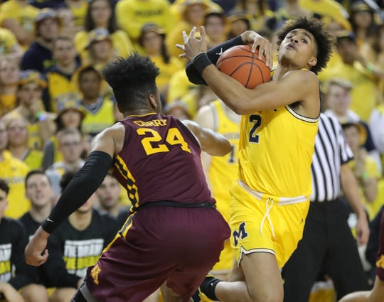 Michigan guard Jordan Poole drives against Minnesota forward Eric Curry during second half action Tuesday, January 22 , 2019 at the Crisler Center in Ann Arbor, Mich.