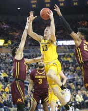 Michigan forward Ignas Brazdeikis drives against  Minnesota guard Amir Coffey during first half action Tuesday, January 22 , 2019 at the Crisler Center in Ann Arbor, Mich.
