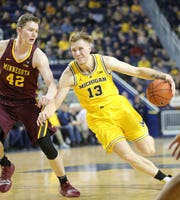 Michigan forward Ignas Brazdeikis drives against  Minnesota guard Michael Hurt during first half action Tuesday, January 22 , 2019 at the Crisler Center in Ann Arbor, Mich.