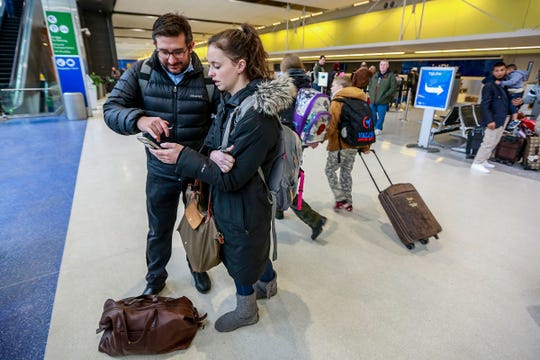 Rodrigo Pereyra, 36, of Salem, Mass. looks over travel options with Kelcey Trecartin, 27, of Salem, after their flight with Jet Blue was cancelled at Detroit Metro Airport on Wednesday, Jan. 23, 2019. The pair are traveling on business an opted to rent a car.
