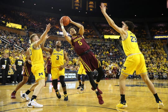 Amir Coffey #5 of the Minnesota Golden Gophers tries to get a shot off around Ignas Brazdeikis #13 and Brandon Johns Jr. #23 of the Michigan Wolverines during the first half at Crisler Arena on January 22, 2019 in Ann Arbor, Michigan.