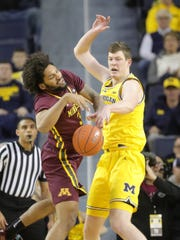Michigan center Jon Teske strips the ball from Minnesota forward Jordan Murphy during first half action Tuesday, January 22 , 2019 at the Crisler Center in Ann Arbor, Mich.
