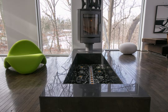 A custom pond and rotating wood-burning German stove that oscillates between the living room and dining room are two features of the two-story contemporary custom-built 4-bedroom home for sale in Ann Arbor Township.