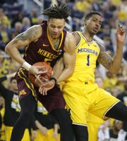 Michigan guard Charles Matthews rebounds against Minnesota guard Amir Coffey during the second half on Tuesday, January 22 , 2019 at Crisler Center in Ann Arbor.