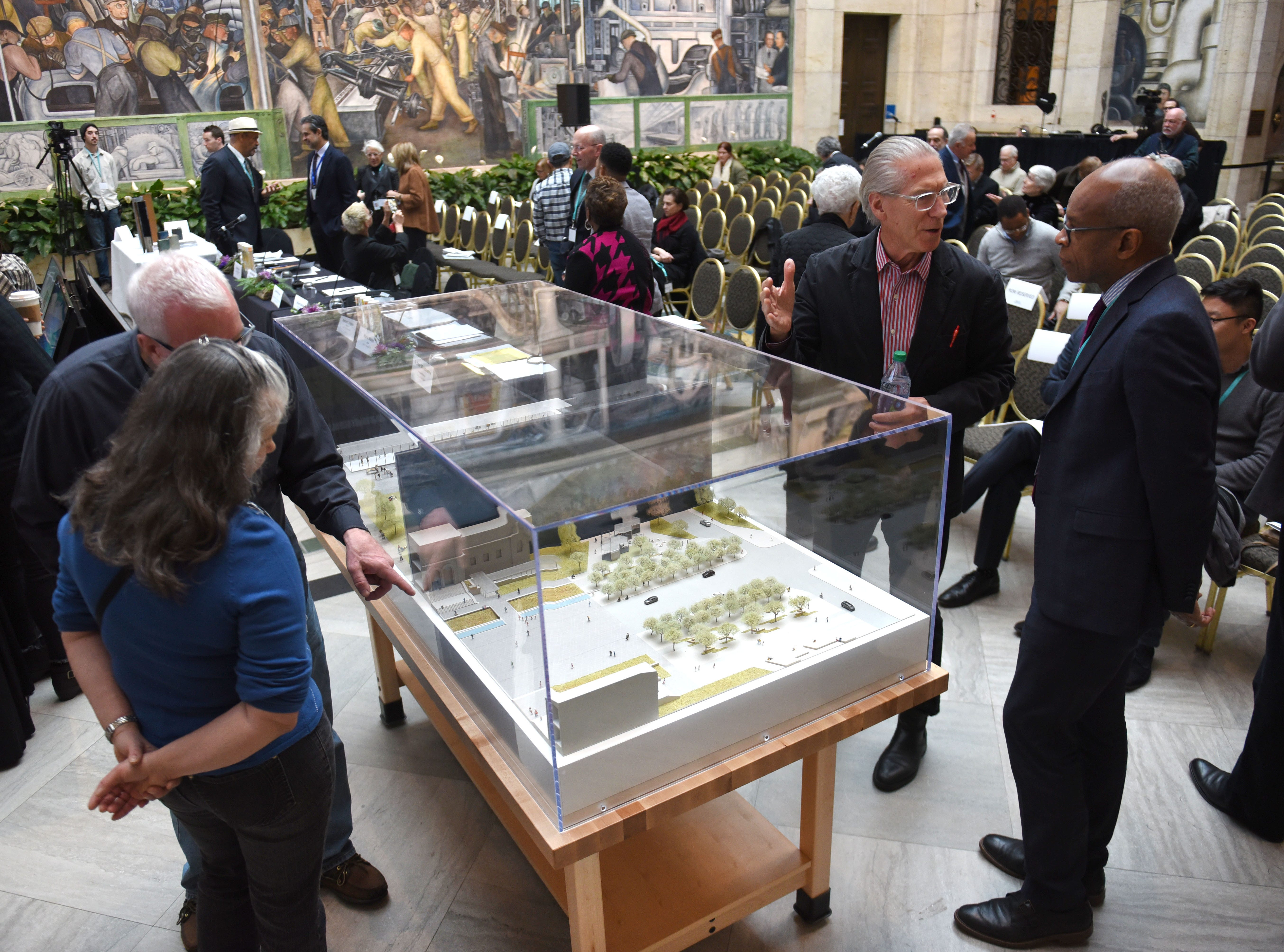 Jamie Carpenter (center), of James Carpenter Design Associates, shows a model by Mikyoung Kim Design to Maurice Cox (right), director of the city of Detroit's Planning Department, for the DIA Plaza which is part of the Midtown Cultural Connections on Wednesday, January 23, 2019.