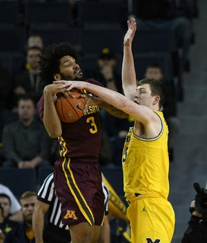 Michigan's Jon Teske blocks a shot attempt by Minnesota's Jordan Murphy, left, in the first half.