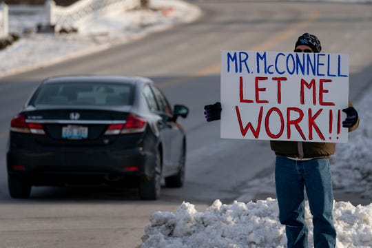 Furloughed EPA worker Jeff Herrema holds a sign outside the offices of U.S. Senator Mitch McConnell, in Park Hills, Ky., Tuesday, Jan 22, 2019.