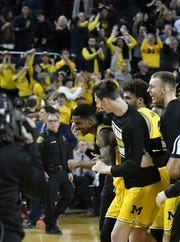 Players celebrate with Charles Matthews, who hit the winning basket as time expired to lift No. 5 Michigan to a 59-57 victory over Minnesota on Tuesday at Crisler Center.