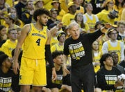 "Coach John Beilein, here speaking with forward Isaiah Livers, wants Michigan to avoid the ""cannibalism"" trend of away teams winning this Tuesday."