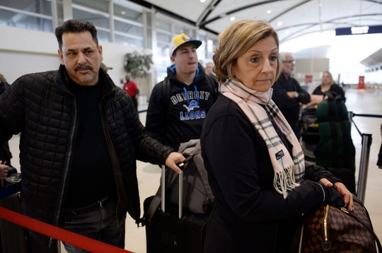 Virginia Selvaggio, 59,  of Clinton Township along with her husband Steve, 59, and son Anthony, 32, (cap on), wait in line to check-in at Detroit Metropolitan Airport after their flight to Orlando was delayed two hours because of the weather on Wednesday,  January 23, 2019 in Romulus.