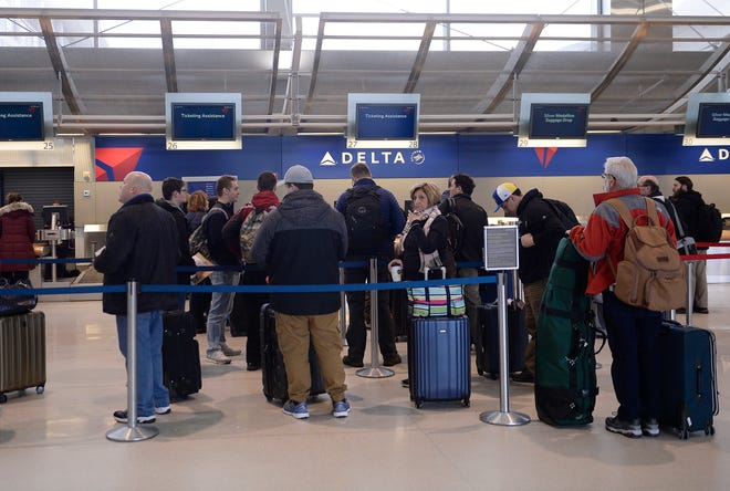 Passengers wait in line at the Delta counter to check in at the McNamara Terminal at Detroit Metro Airport in Romulus in January.