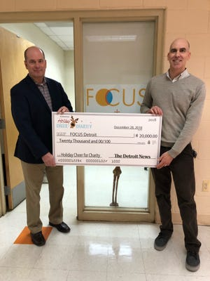 Nolan Finley, left, presents a  $20,000 check to Focus Detroit founder Eric Shanburn on Friday, January 18. 2019.