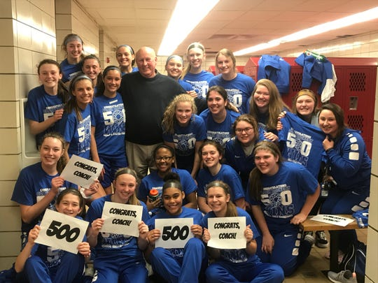 The Memorial girls' basketball team celebrates coach Bruce Dockery's 500th career victory. He is the sixth girls' coach in state history to reach the milestone.