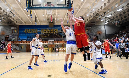 Mater Dei's Logan Carter (23) shoots over Castle's Brodey Heaton (44) as the Mater Dei Wildcats play the Castle Knights in Paradise Tuesday, January 22, 2019.